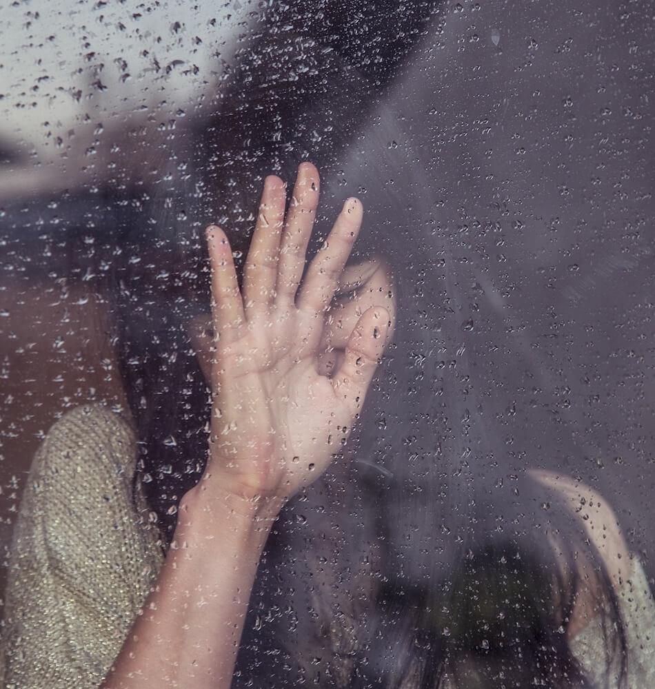Uplašena žena iza stakla sa kapljicama kiše