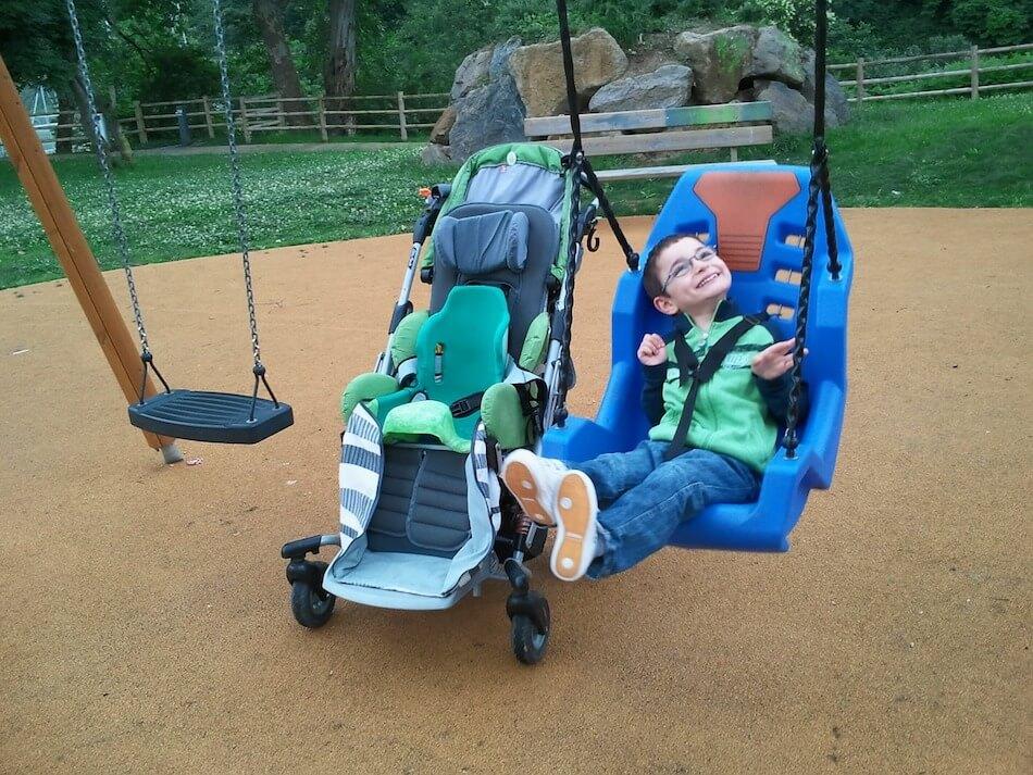 Invalidno dijete koje je smješteno i pričvršćeno u ljuljački