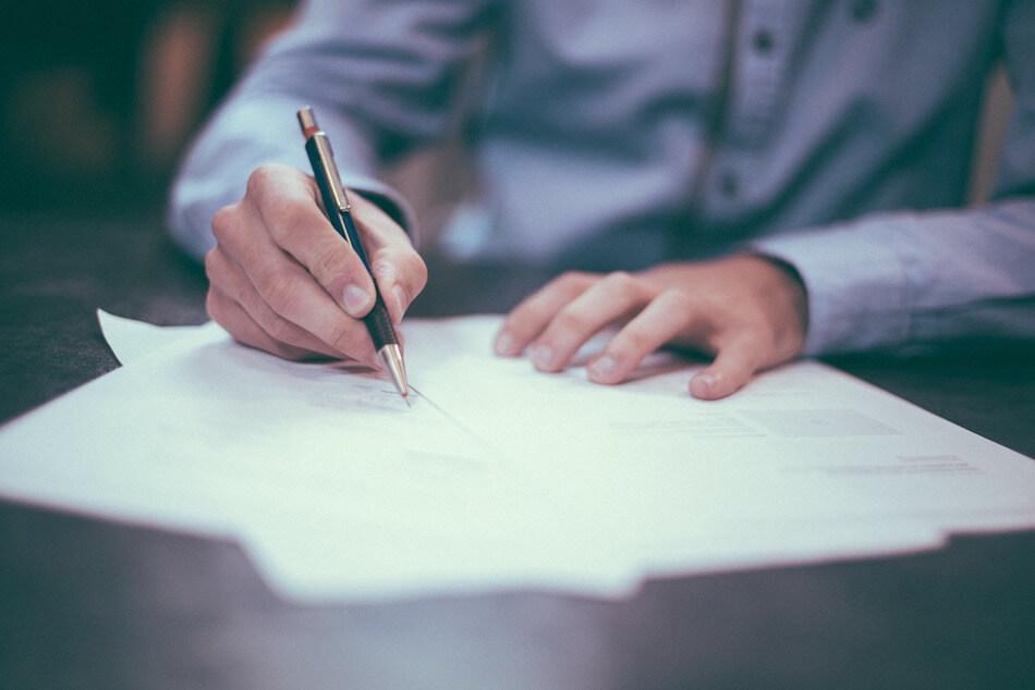 Na fotografiji su prikazane muške ruke sa olovkom nad papirima na stolu