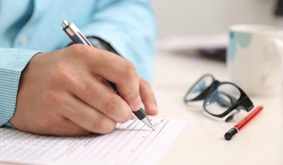 Na slici je muška ruka sa olovkom u ruci koja na stolu popunjava obrazac
